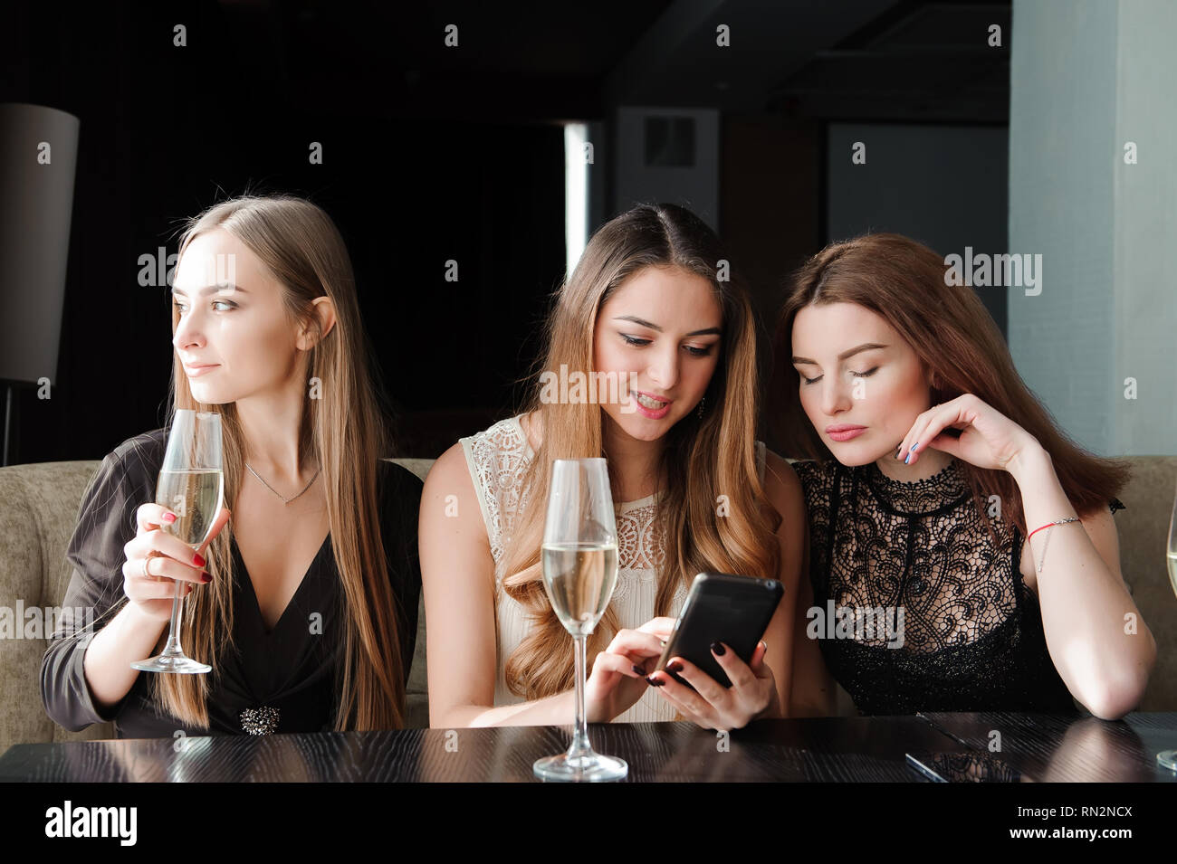 always connected, internet addiction, young girls in cafe - Stock Image
