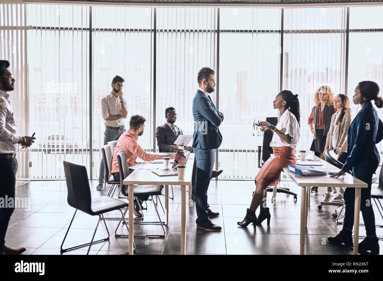 beautiful woman and handsome man talking in the office room while their colleagues are looking at them. conversation. woman and man sharing with exper - Stock Image