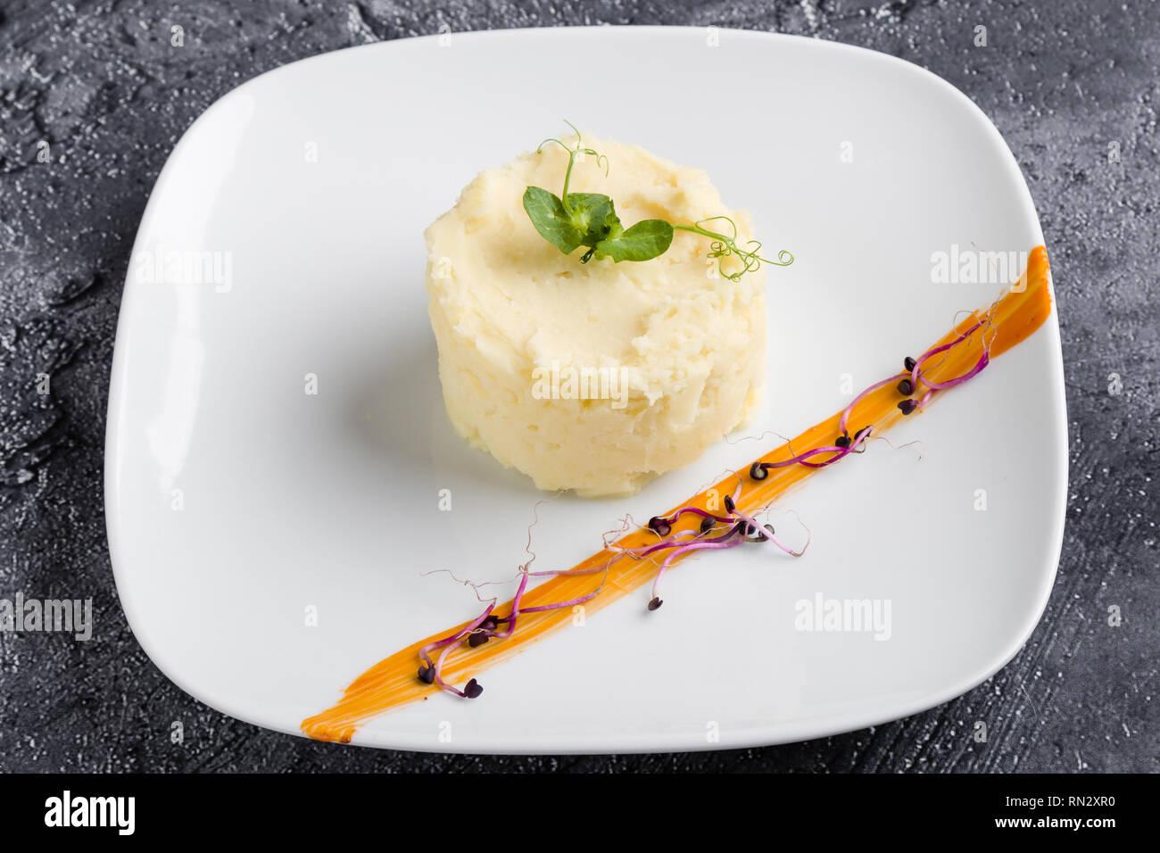 fresh mashed potato portion on white plate - Stock Image