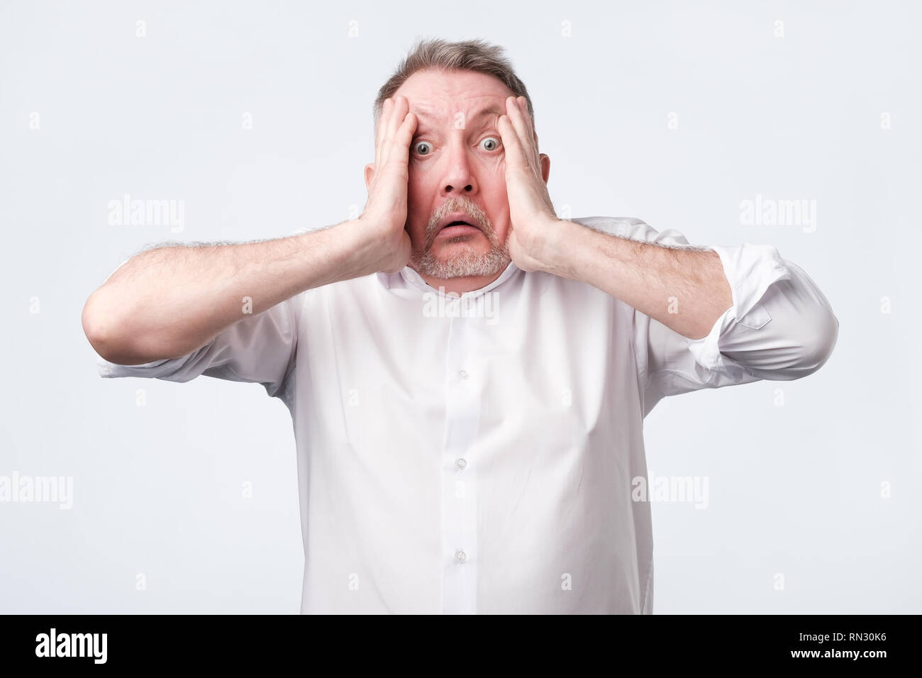 Crazy desperate senior man being shocked looking at camera trembling with fear. - Stock Image