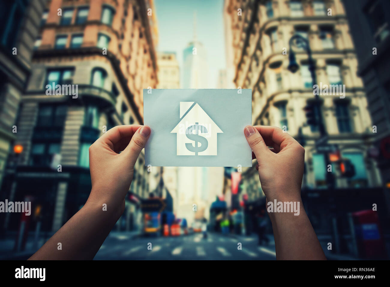 Poverty and homelessness global issue concept as woman hands holding a paper sheet with house and dollar icon inside in the middle of the street of a  - Stock Image