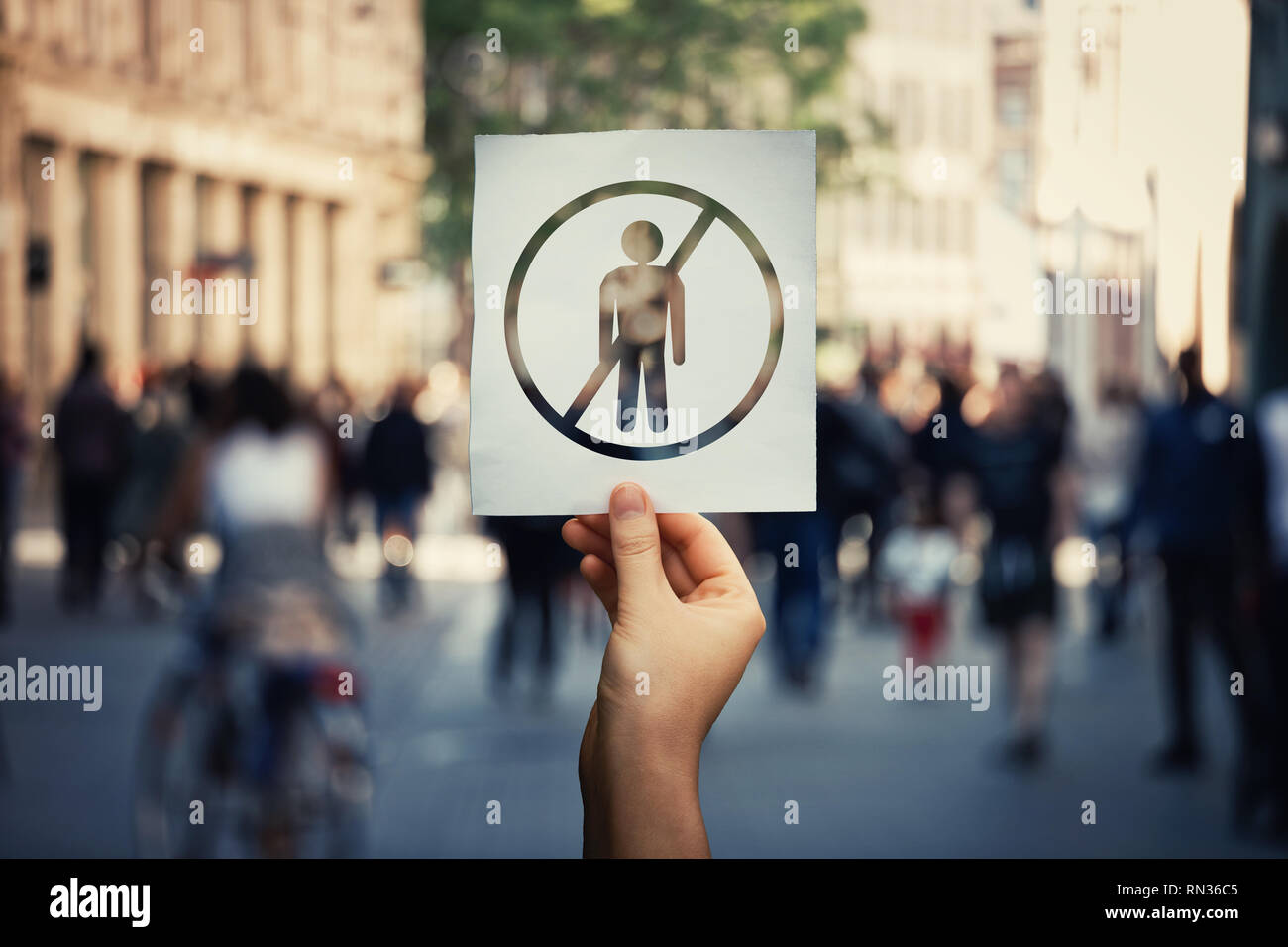 Unemployment global issue as hand holding a paper sheet with person employee icon over a crowded street background. Social problem, lack of economic o - Stock Image