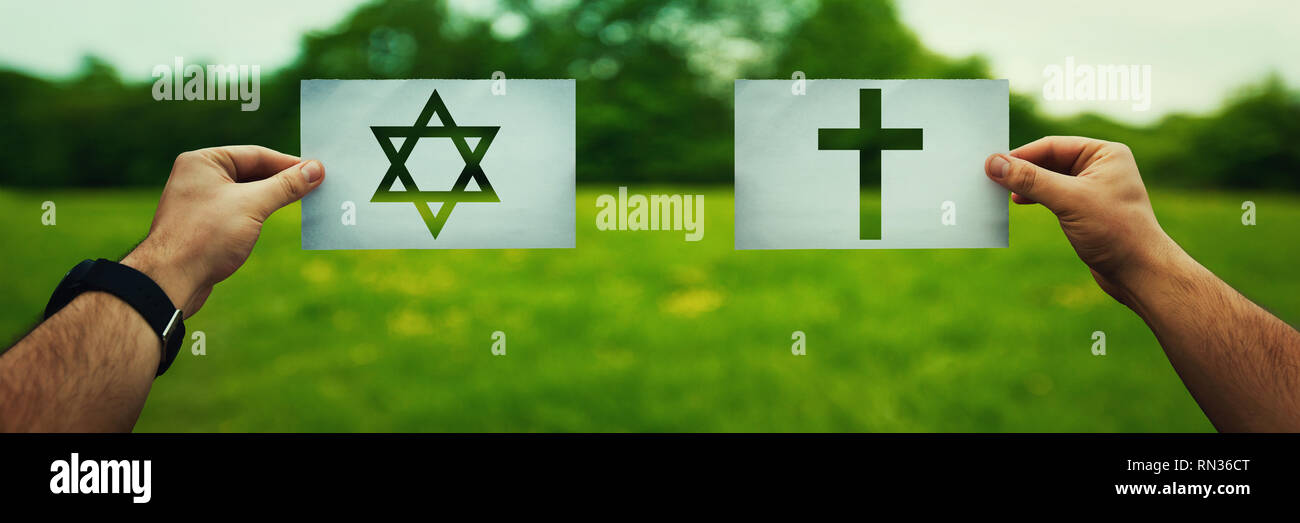 Religion conflicts as global issue concept. Two hands holding different faith symbols, Judaism vs Christianity belief over green field nature. Relatio - Stock Image