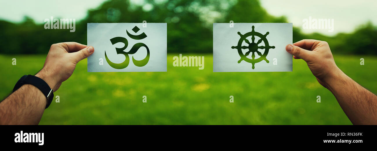Religion conflicts as global issue concept. Two hands holding different faith symbols, Buddhism vs Hinduism belief over green field nature. Relations  - Stock Image