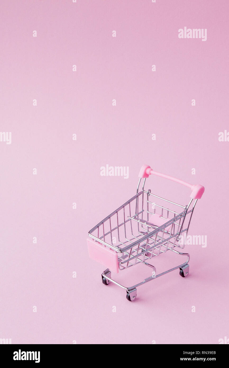 Small supermarket grocery push cart for shopping toy with wheels and pink plastic elements on pink pastel color paper flat lay background. Concept of  Stock Photo