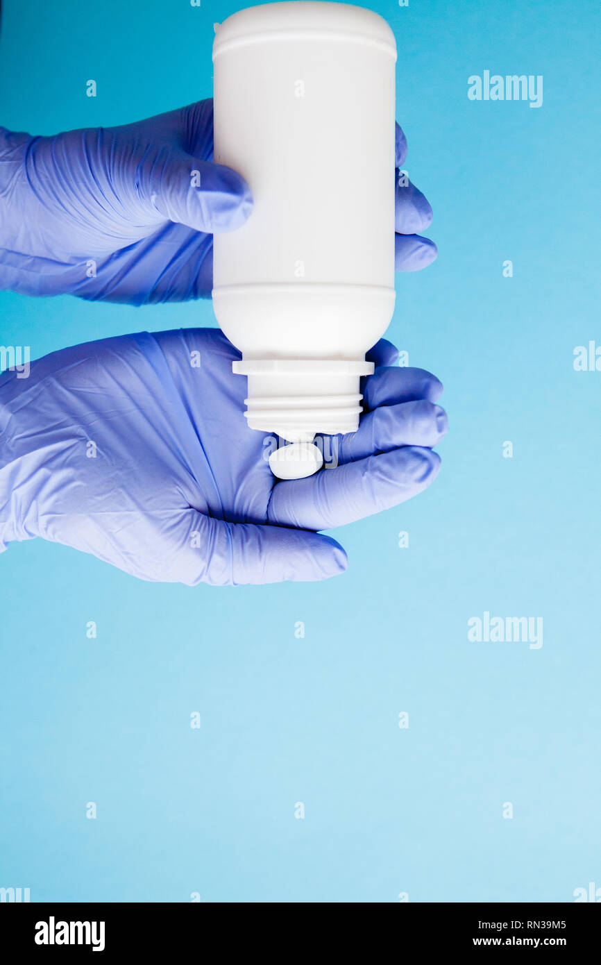 Doctor's holding cupped hand full of pills, view from above. - Stock Image