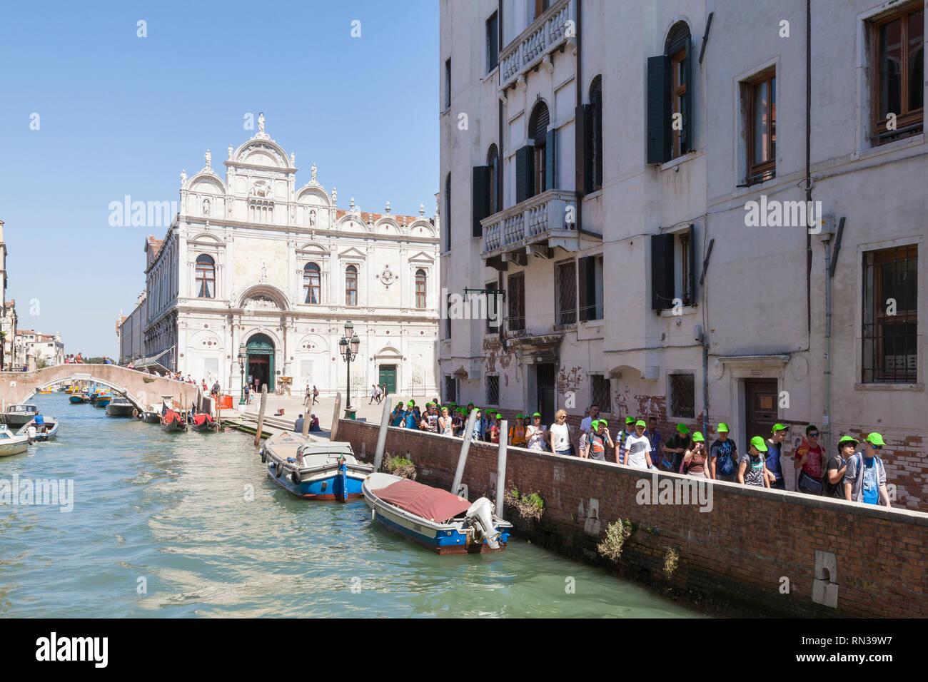 Tour group walking through Castello, Venice, Italy on a  canal in front of Campo dei Santi Giovanni e Paolo and Scuola Grande di San Marco - Stock Image