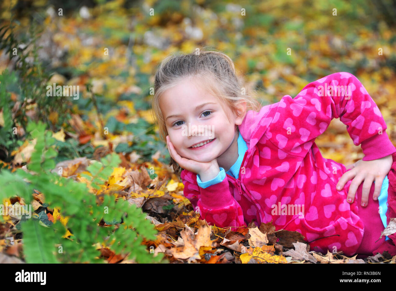 Beautiful young girl plays in the leaves outdoors on a Fall day.  She is wearing hot pink and leaning on an elbow surrounded by Fall color. - Stock Image