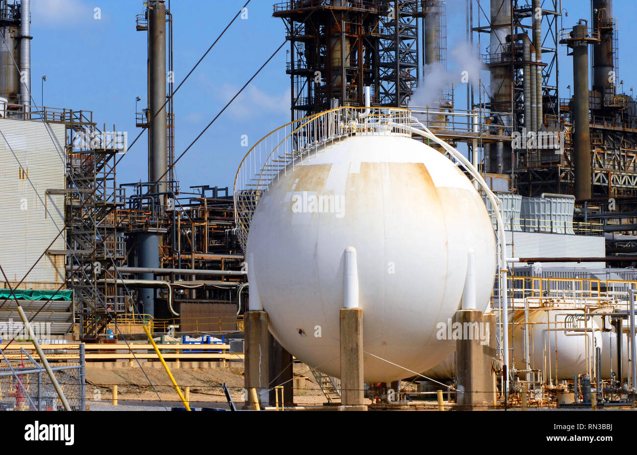 Large white storage tank at oil refinery has spiral stairs winding around base to top of tank. - Stock Image