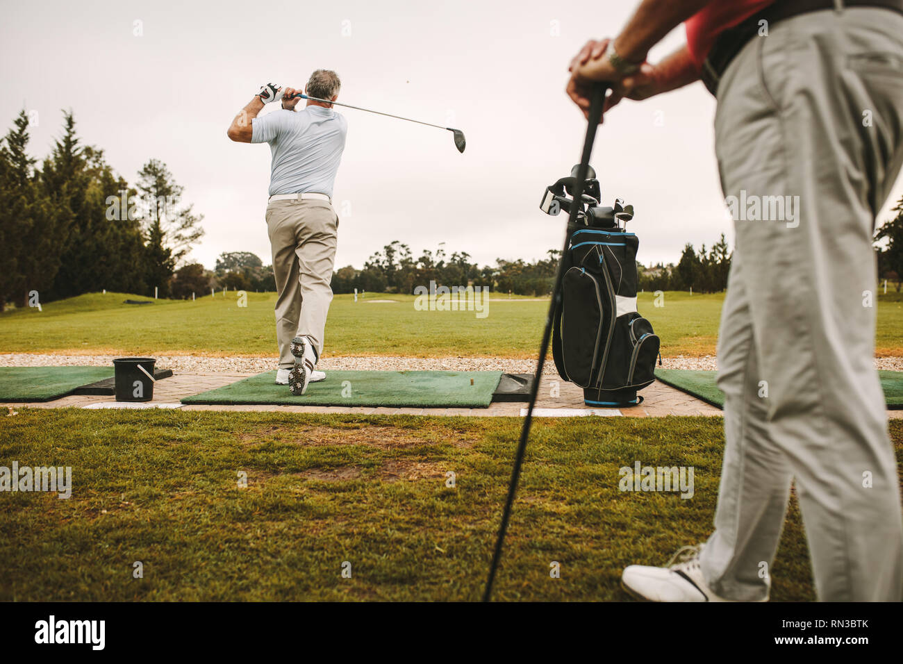 Senior man at a driving range playing golf and practice his swing with other man standing in front. Senior male golfers practicing at golf course. - Stock Image