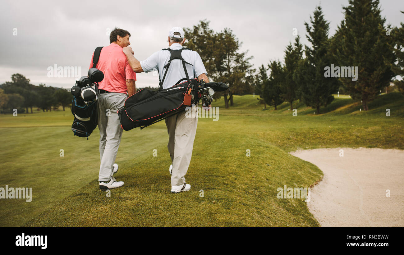 Rear view of two senior golf players walking together in the golf course with their golf bags. Senior golfers walking towards the next hole. - Stock Image