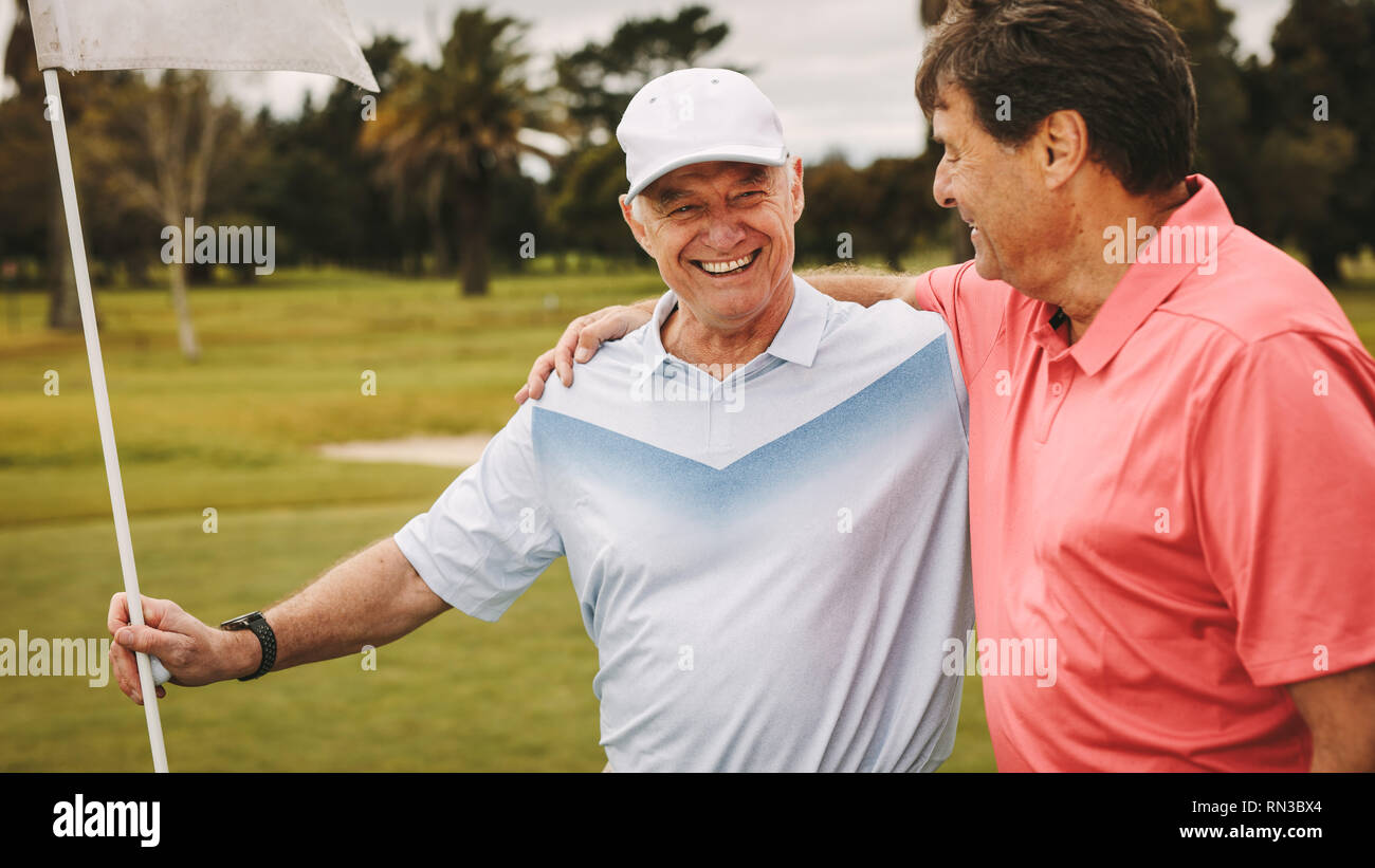 Golfing friends on the putting green at the golf course. Two senior golfer on the golf course standing together with flag. - Stock Image