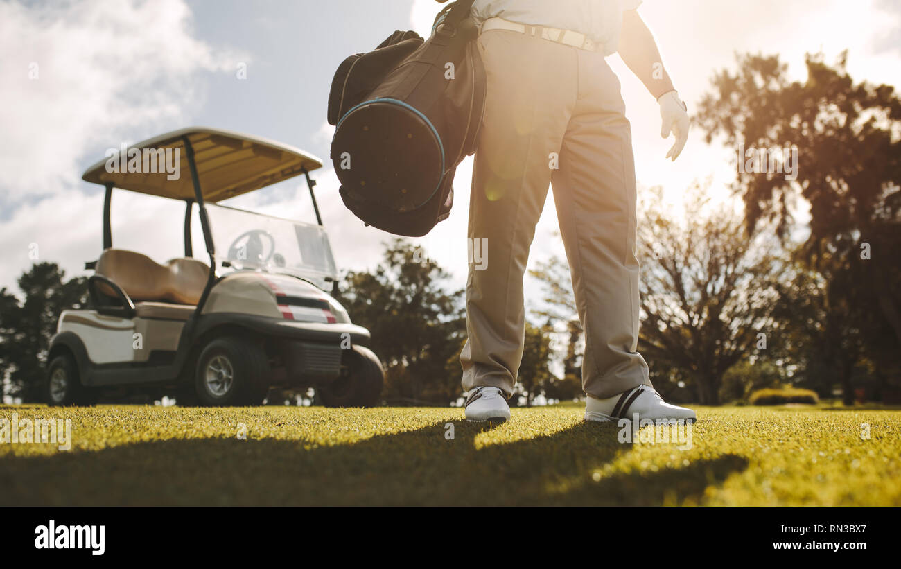 Low angle shot of man standing on the lawn with his golf bag and a golf cart at the back. Male golfer on the court after the game. - Stock Image