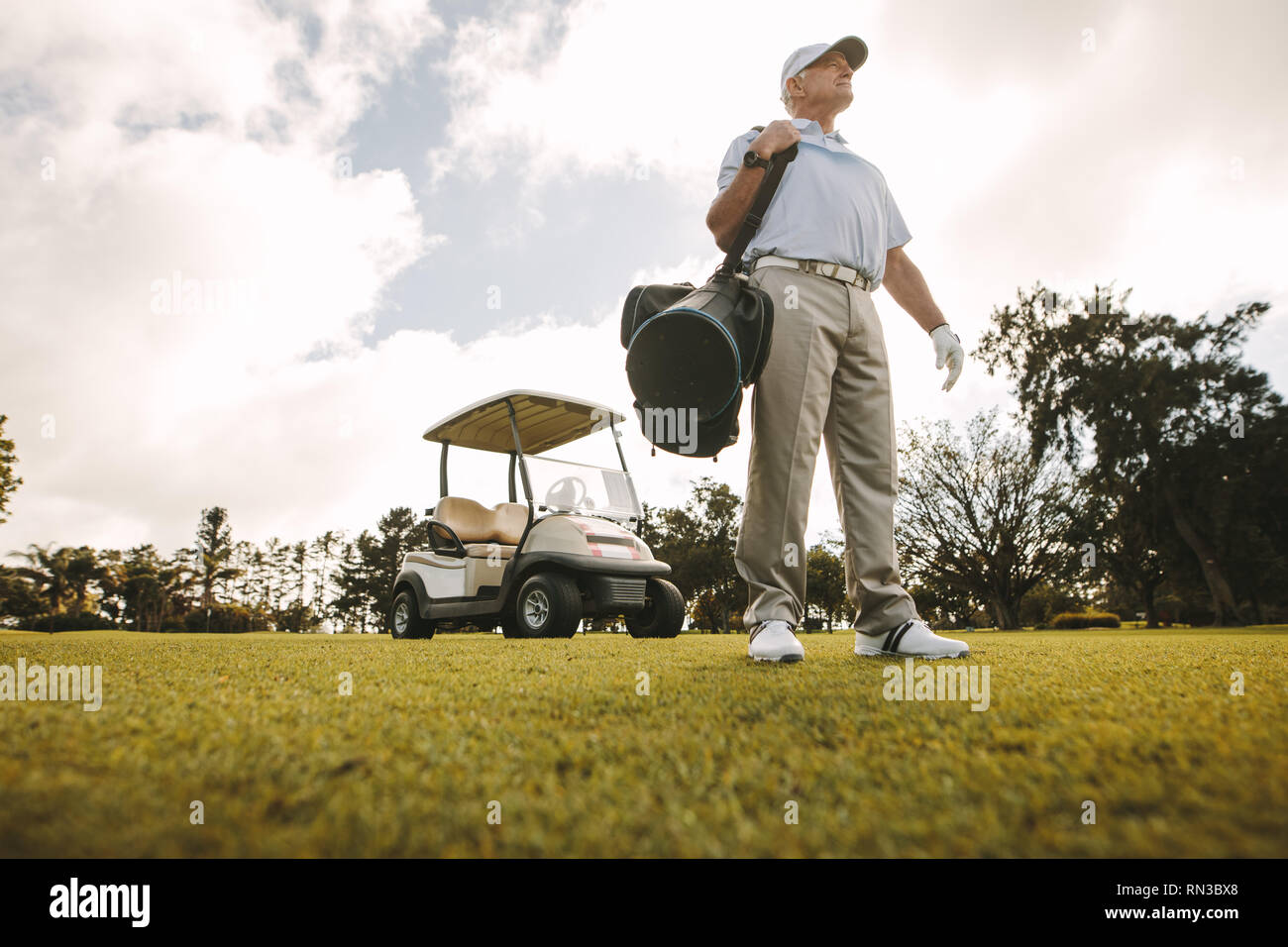 Low angle shot of senior male golfer standing on the golf course with his golf bag and a golf cart at the back. Male golfer carrying golf bag on the g - Stock Image