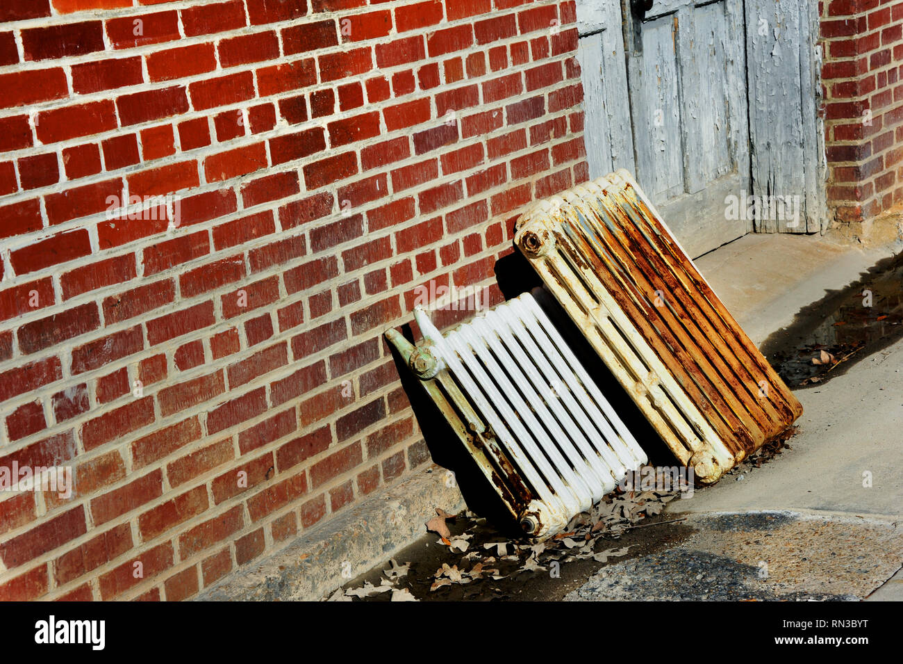 Old iron radiant heaters lay discarded against brick wall.  Heaters are being replaced by more up-to-date heating options. - Stock Image