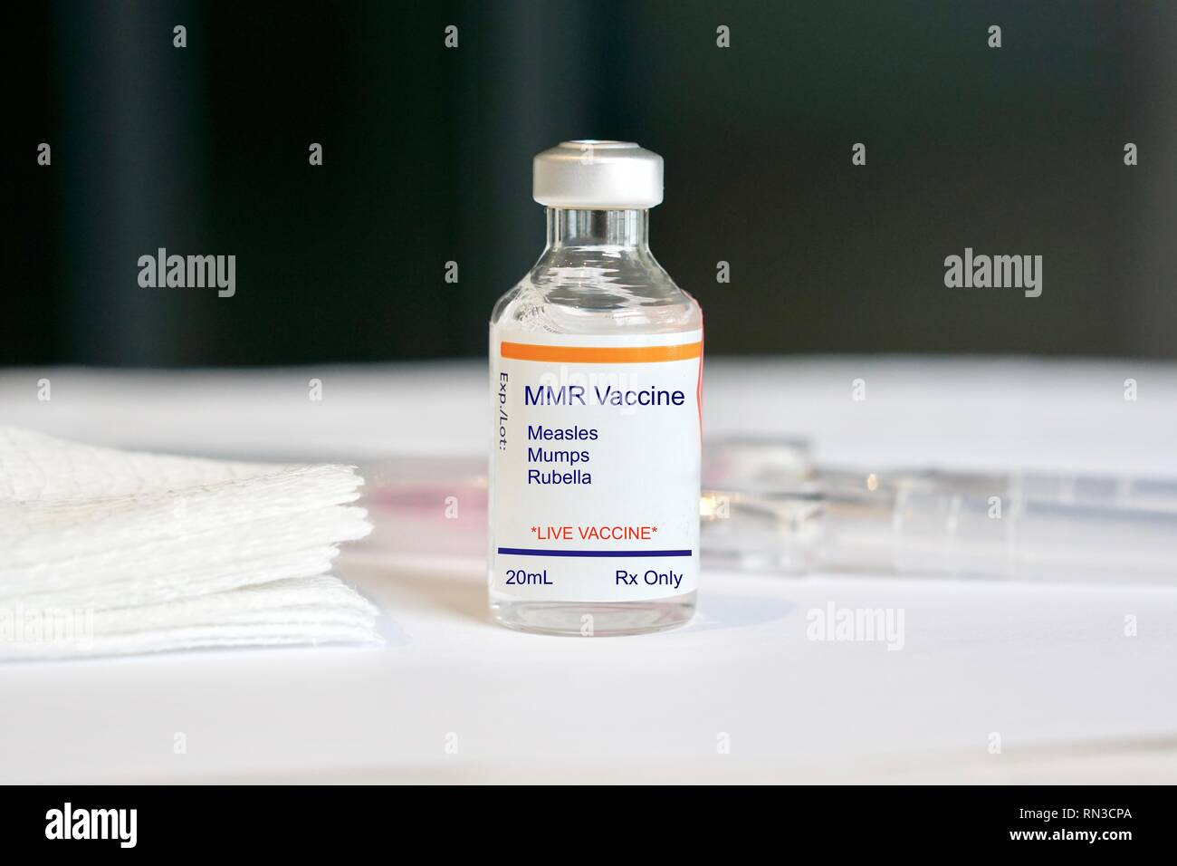 MMR Vaccine for measles, mumps, and rubella in a glass vial in a medical setting - Stock Image