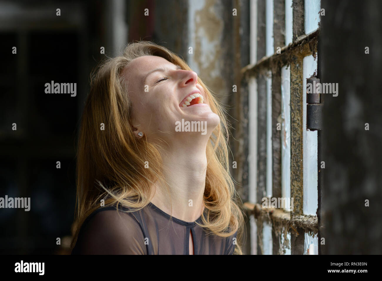 Happy amused young woman enjoying a good laugh with her head thrown back and closed eyes in front of a large rustic window indoors Stock Photo