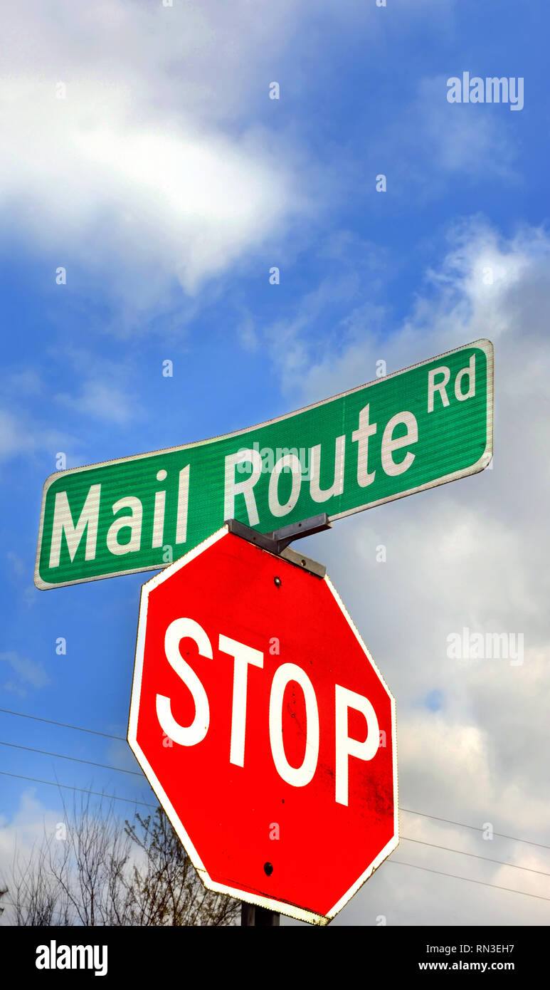 Low angle shot of road sign leaves plenty of room for personalization.  Sign says 'Mail Route Road.'  Blue sky and clouds fill photo. - Stock Image
