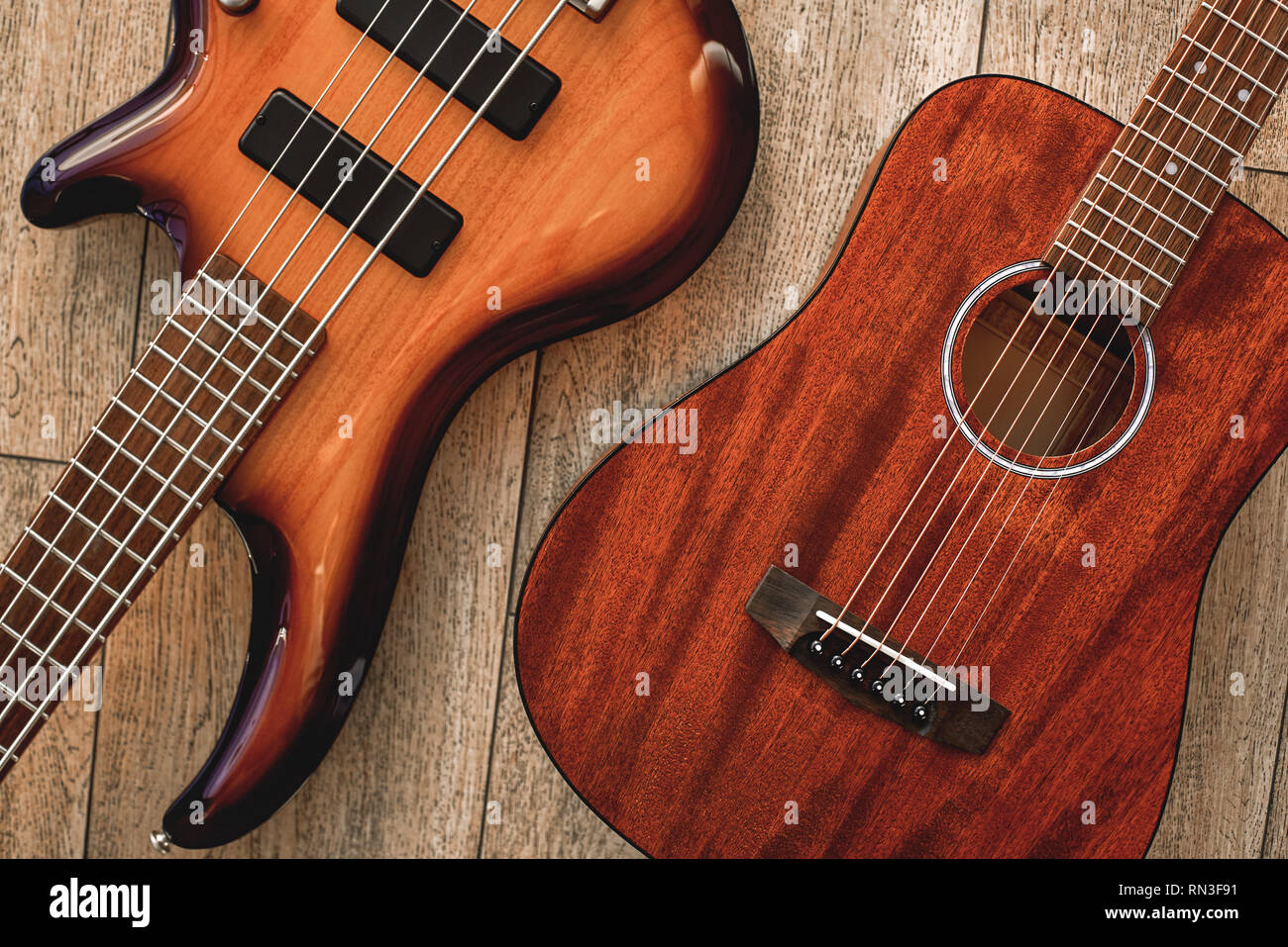 What to choose Top view on two cool musical instruments: acoustic and electric guitars are lying on the wooden floor in a music shop. Musical instruments. Music concept. - Stock Image