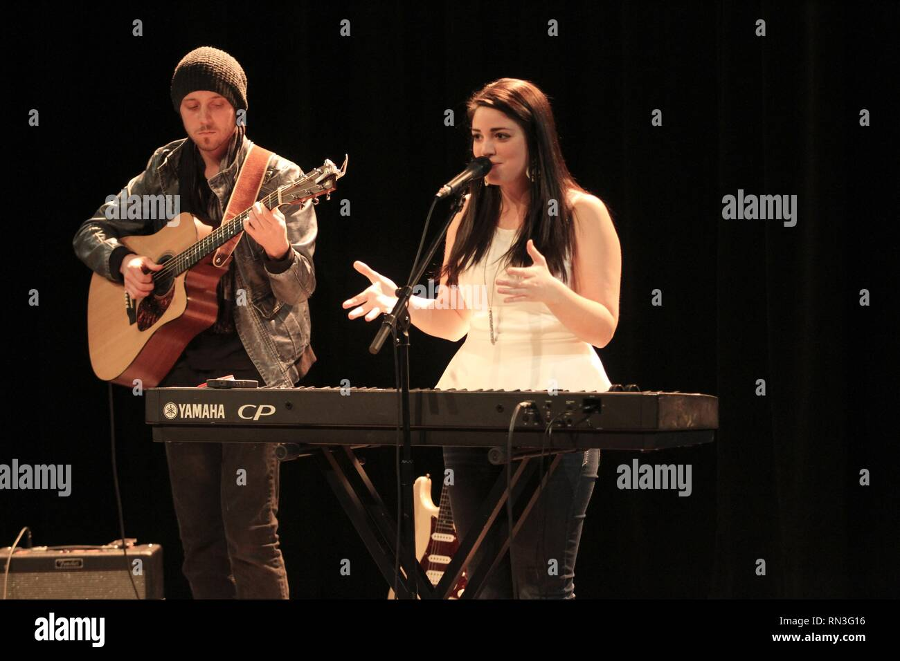 Musicians Alyssa Rose Coco and Matt Merritt are shown performing on stage during a 'live' concert appearance as Roses and Revolutions. - Stock Image
