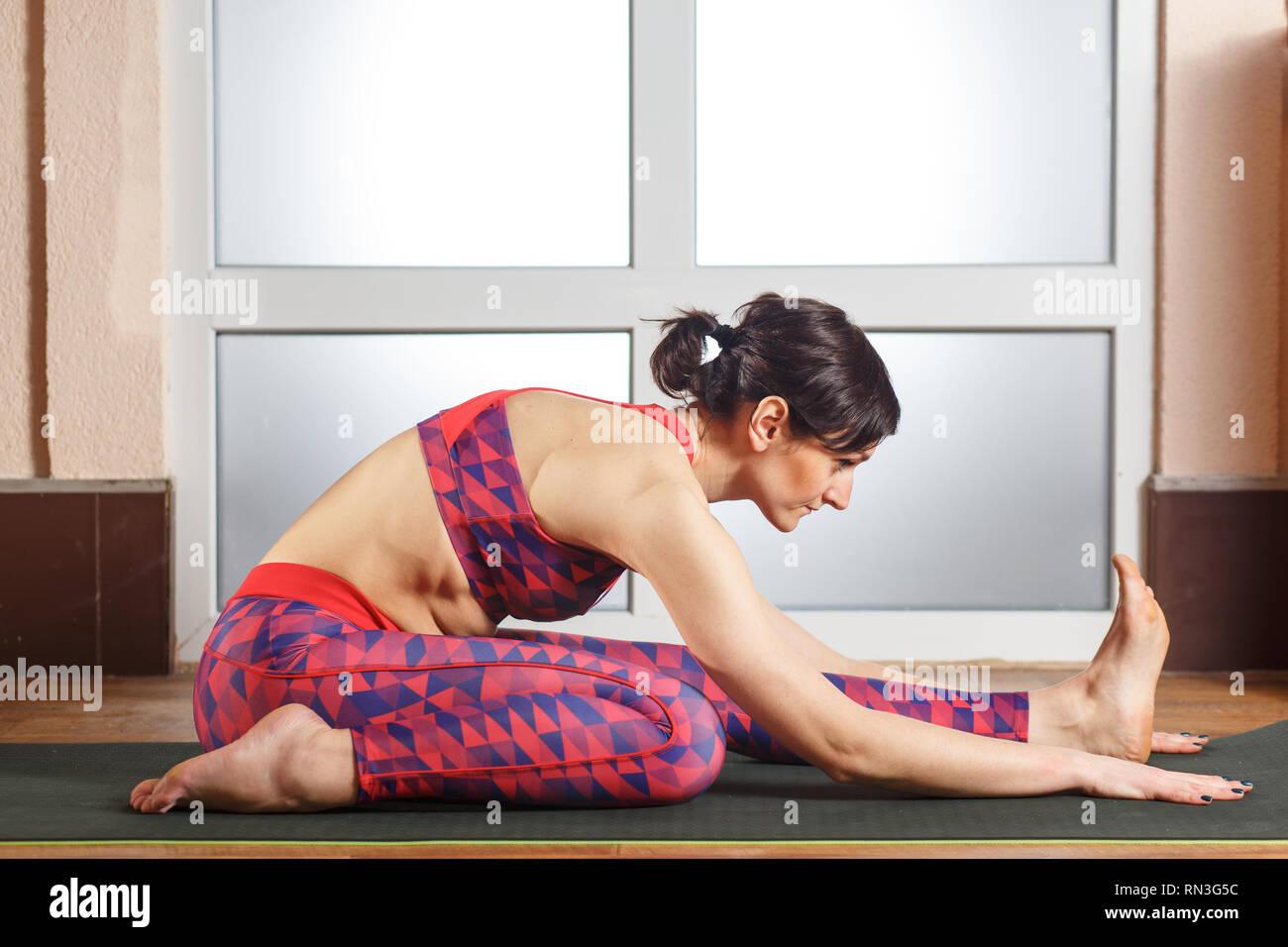 Young sporty woman practicing yoga, doing doing Ashtanga Vinyasa yoga Tiryam-Mukha Eka-Pada Paschimottanasana asana stretching position in a fitnes cl - Stock Image
