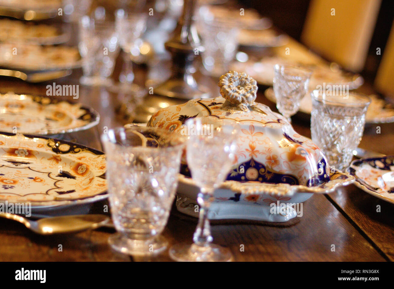 Antique glasses and porcelain on a laid table at Scotney castle, Kent, UK. - Stock Image