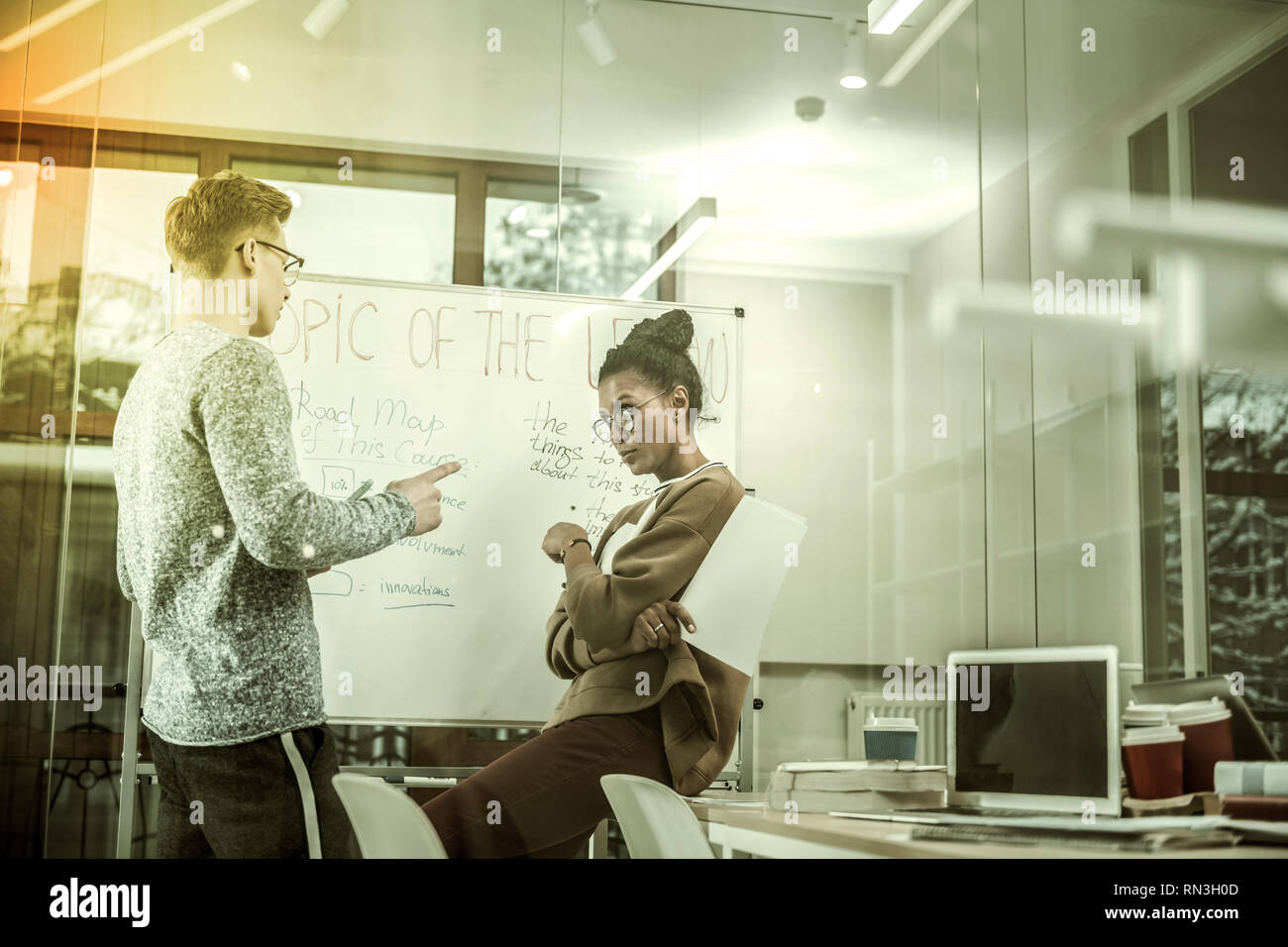 Two coworkers discussing topic of the day in their modern office - Stock Image