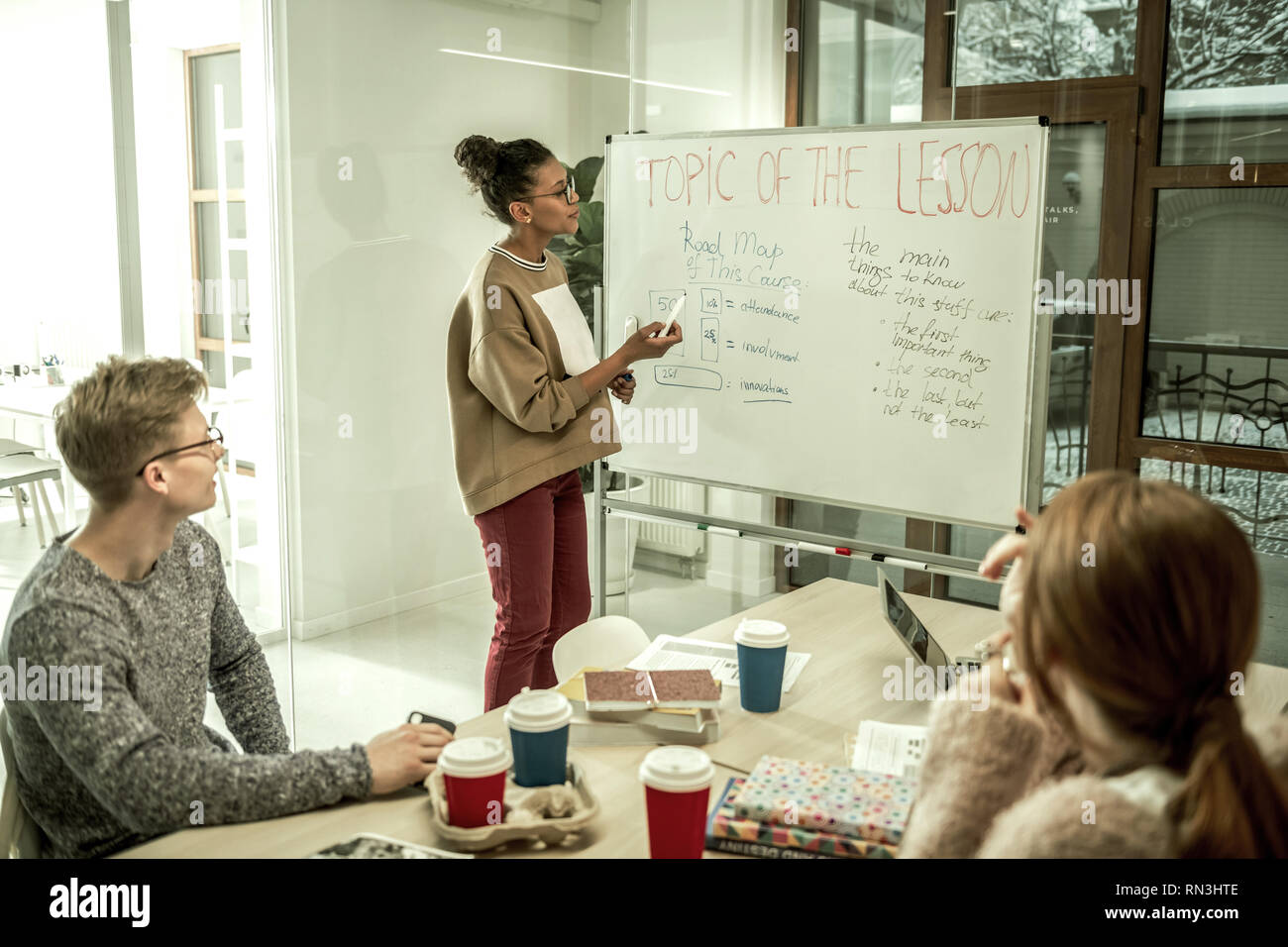 Young smart teacher explaining topic of the lesson to her students - Stock Image