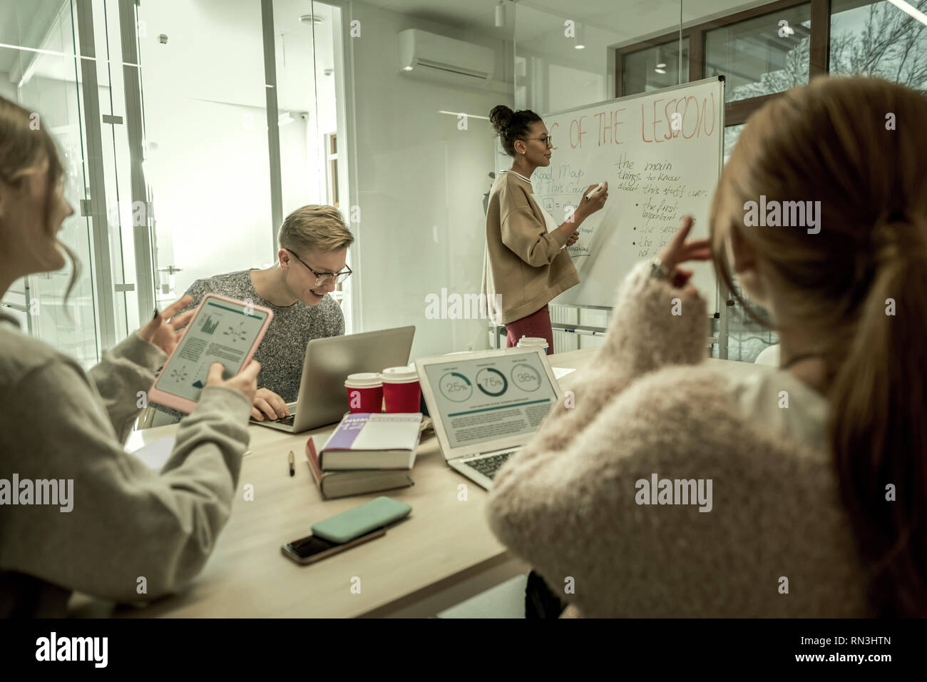 Three modern students using their gadgets during the class - Stock Image