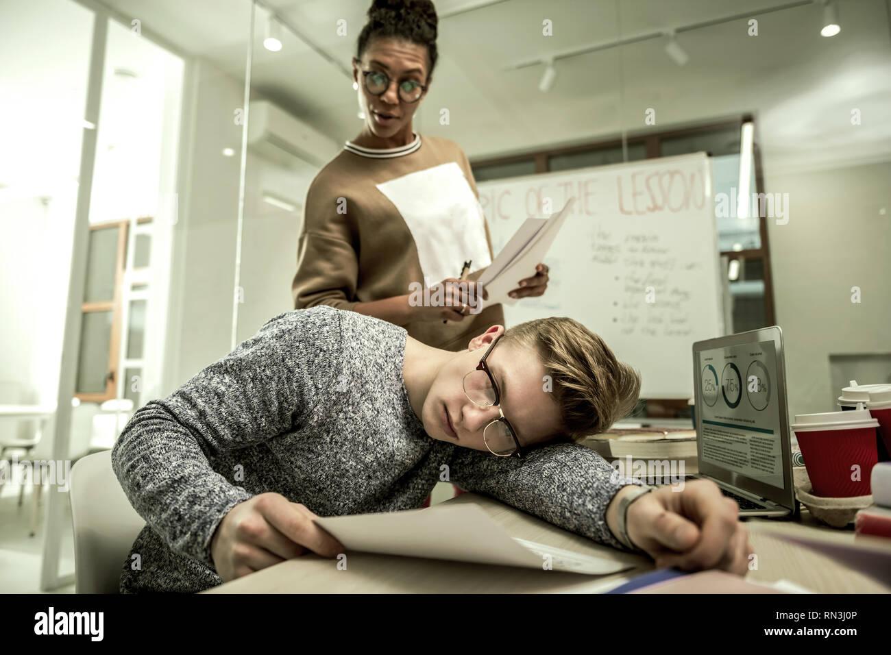 Student pretending not to listen to his teacher standing near him - Stock Image