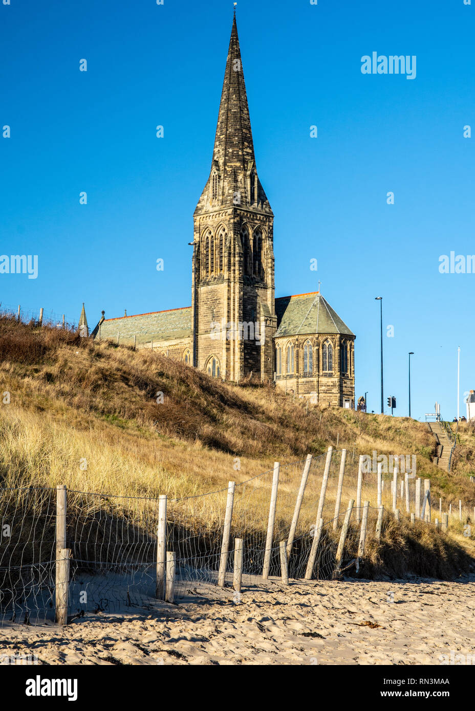 St George's Church spire rises above the sandy beach of Tynemouth Longsands at Cullercoats in Tyneside. - Stock Image