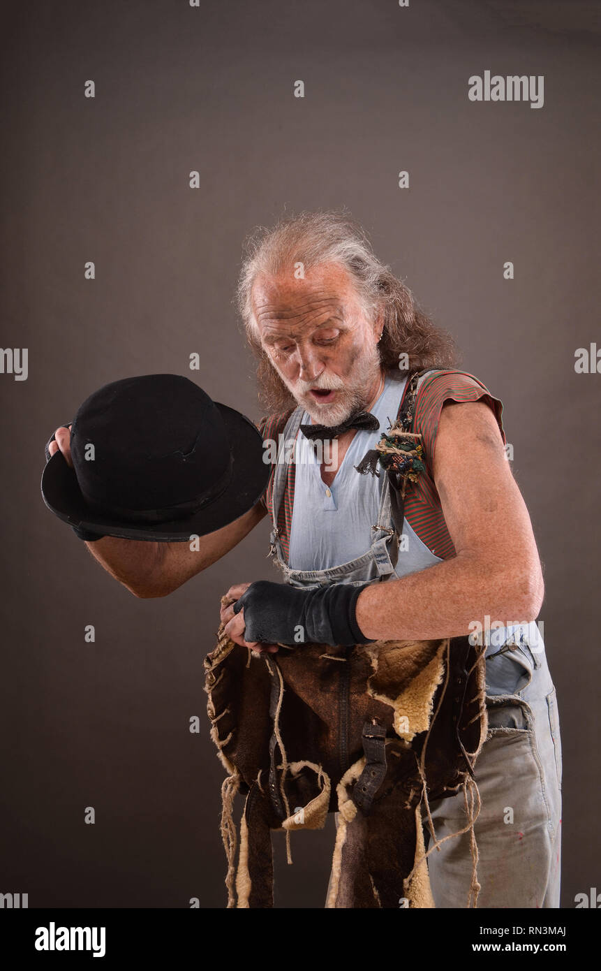 Old homeless tramp wearing jeans, black gloves and hat, carrying shabby lleather bag - Stock Image