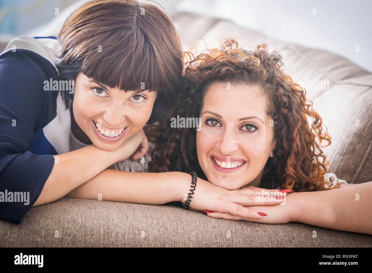 nice time and happiness with laugh and smiles for two caucasian female friends lay down together on the sofa at home. friendship concept for indoor pi - Stock Image