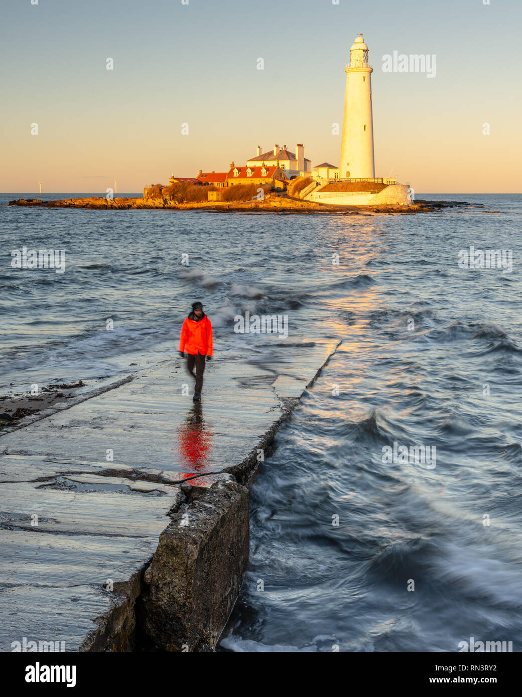 A man stands on the St Mary's Island Causeway while the setting sun illuminates St Mary's Lighthouse on the coast of Whitley Bay in Tyneside. Stock Photo
