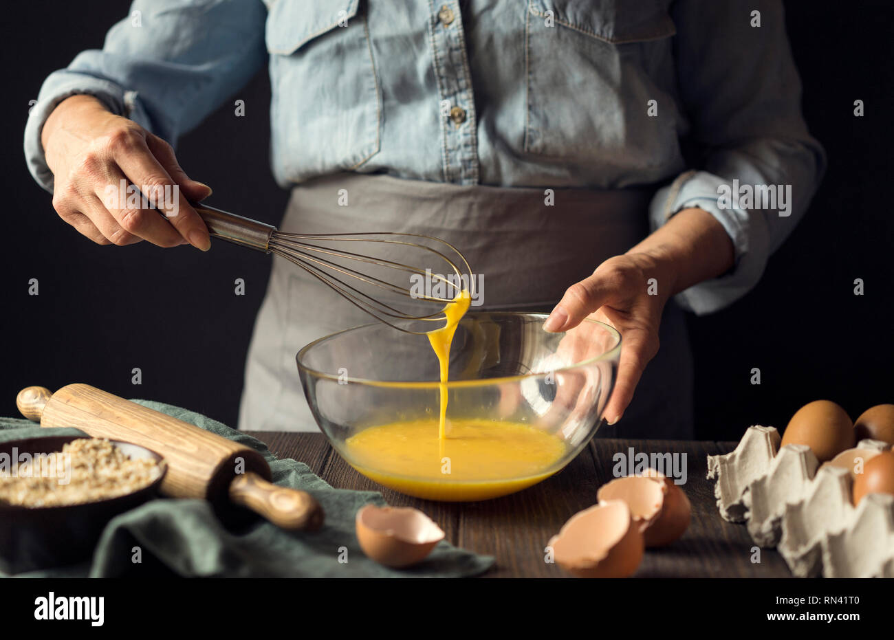 Hands of man whisking bowl of eggs - Stock Image