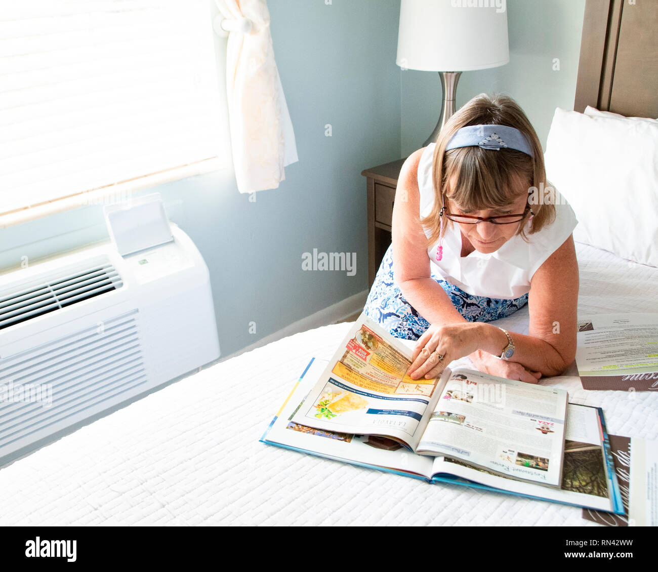 Senior woman sitting on a bed in a hotel looking at travel magazines.  Planning her day. - Stock Image
