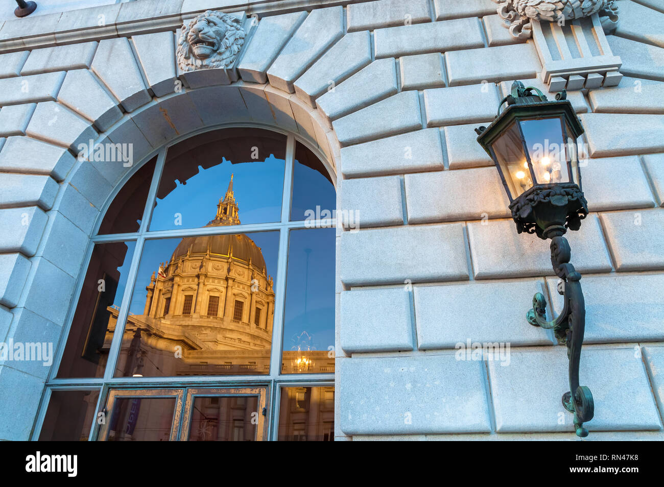 Reflections of the San Francisco City Hall on the glass window of The  War Memorial Opera House, and a wall light sconce, California, USA - Stock Image