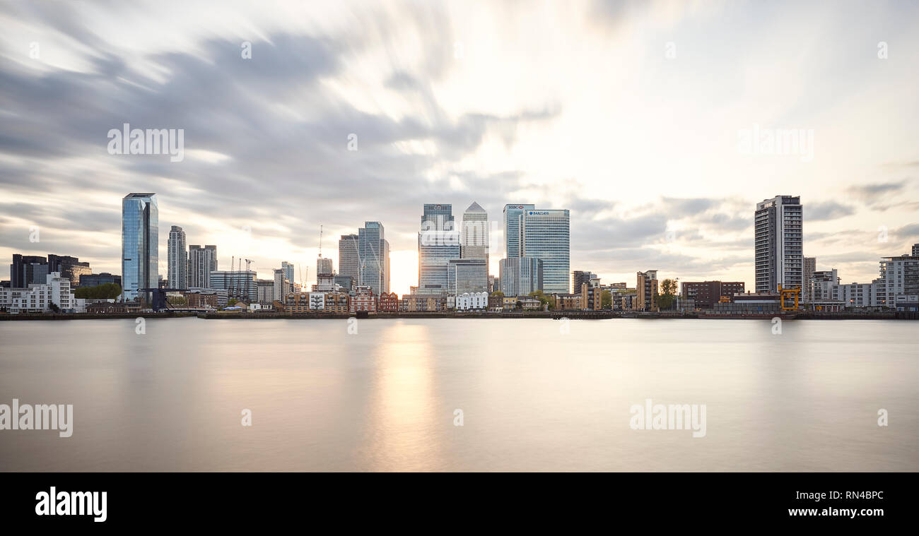 The Skyline of Canary Wharf, London, with the sun setting behind the offices of this fanancial district - Stock Image