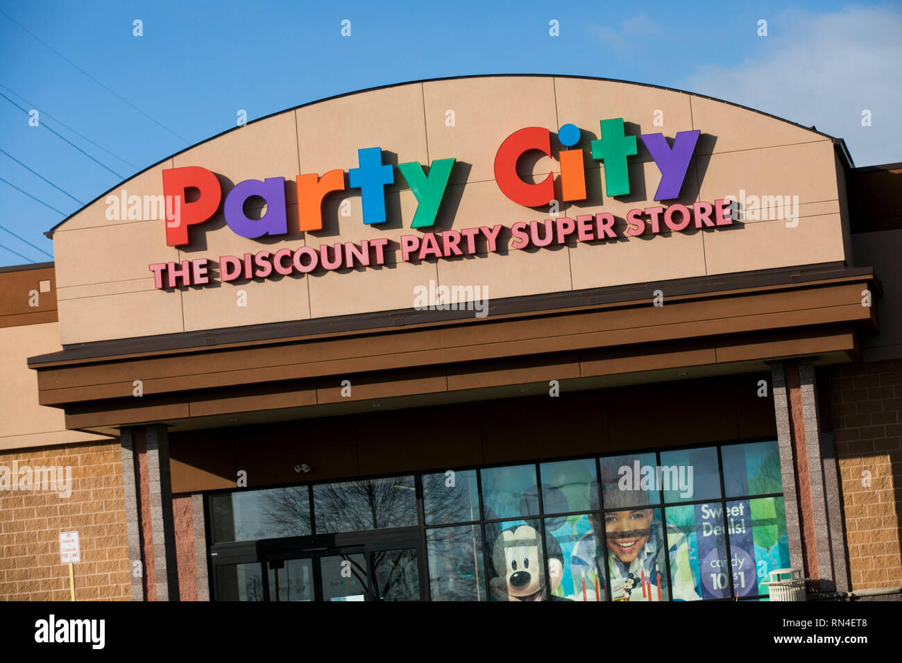 A logo sign outside of a Party City retail store location in