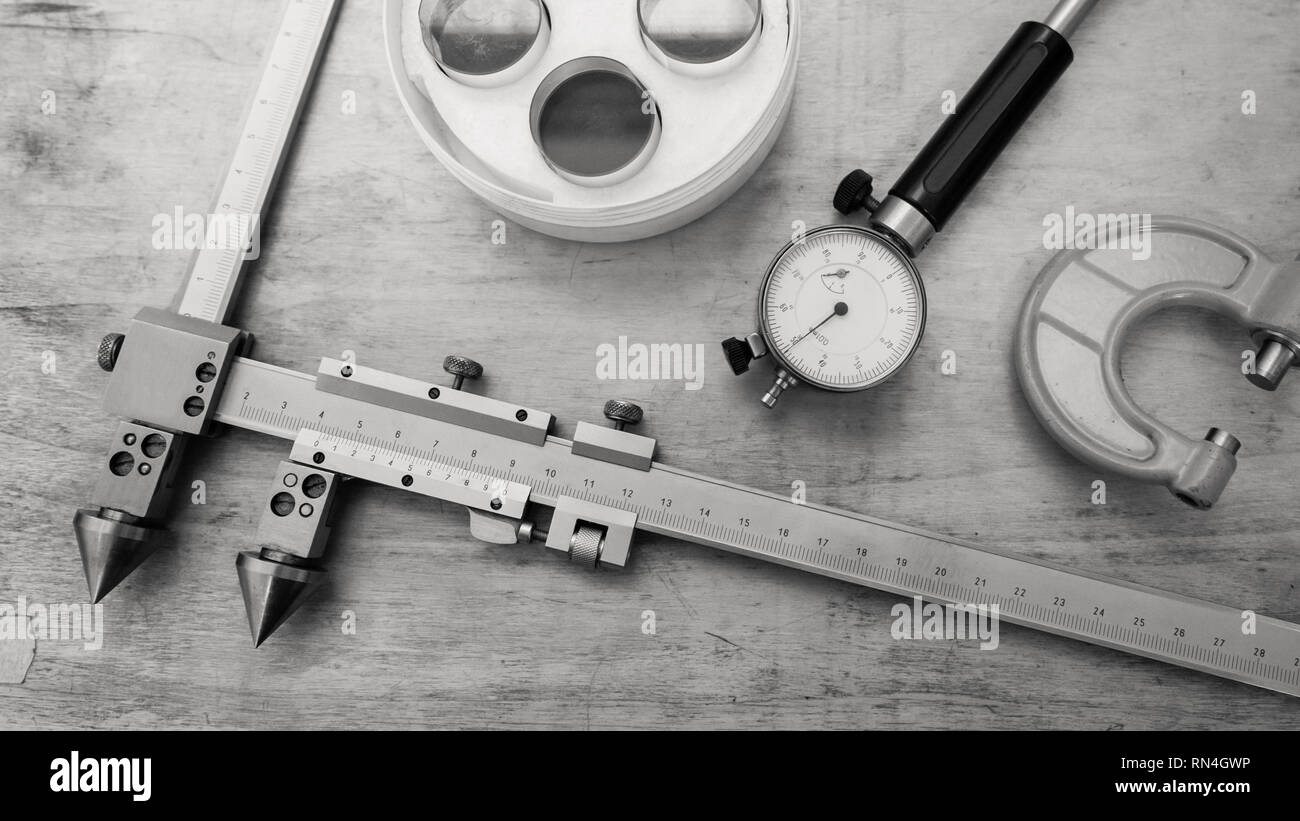 Metal measuring instruments on a wooden table. Product quality control. Black and white. - Stock Image