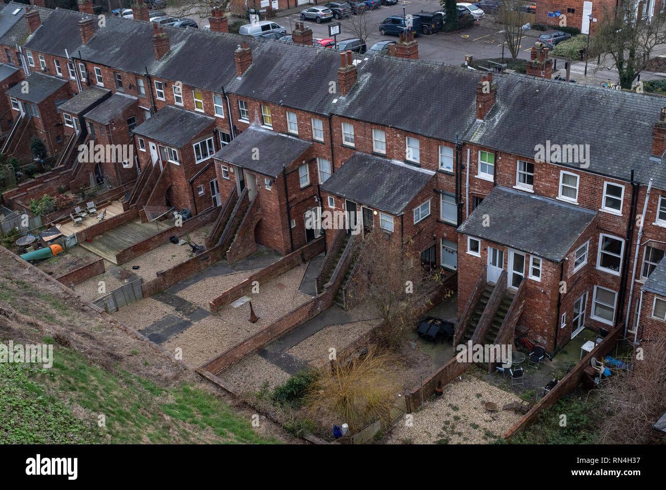 A high viewpoint of a row of terraced houses in the UK seen from the back. - Stock Image