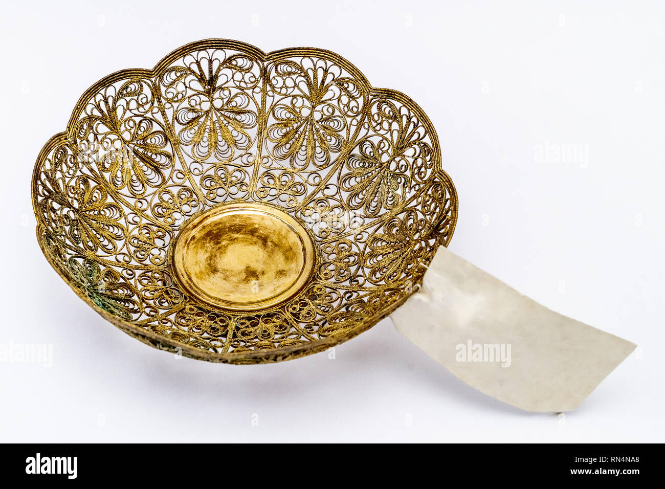 Vintage metal openwork gold vase with label on a white background. Top view - Stock Image