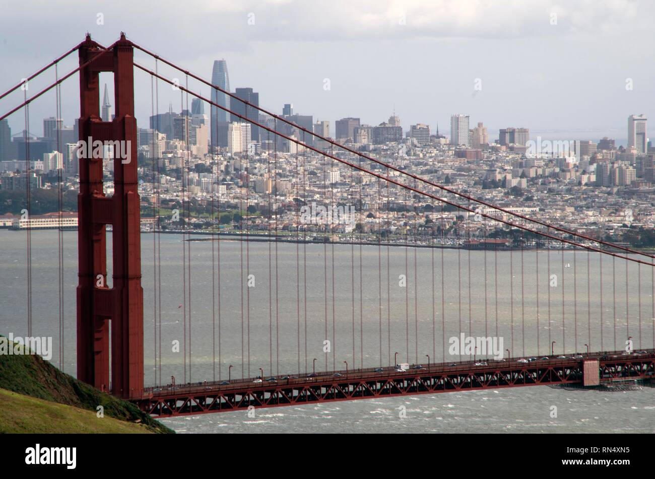 The city of San Francisco provides a nice backdrop to the Golden Gate Bridge, seen from the Marin Headlands. - Stock Image