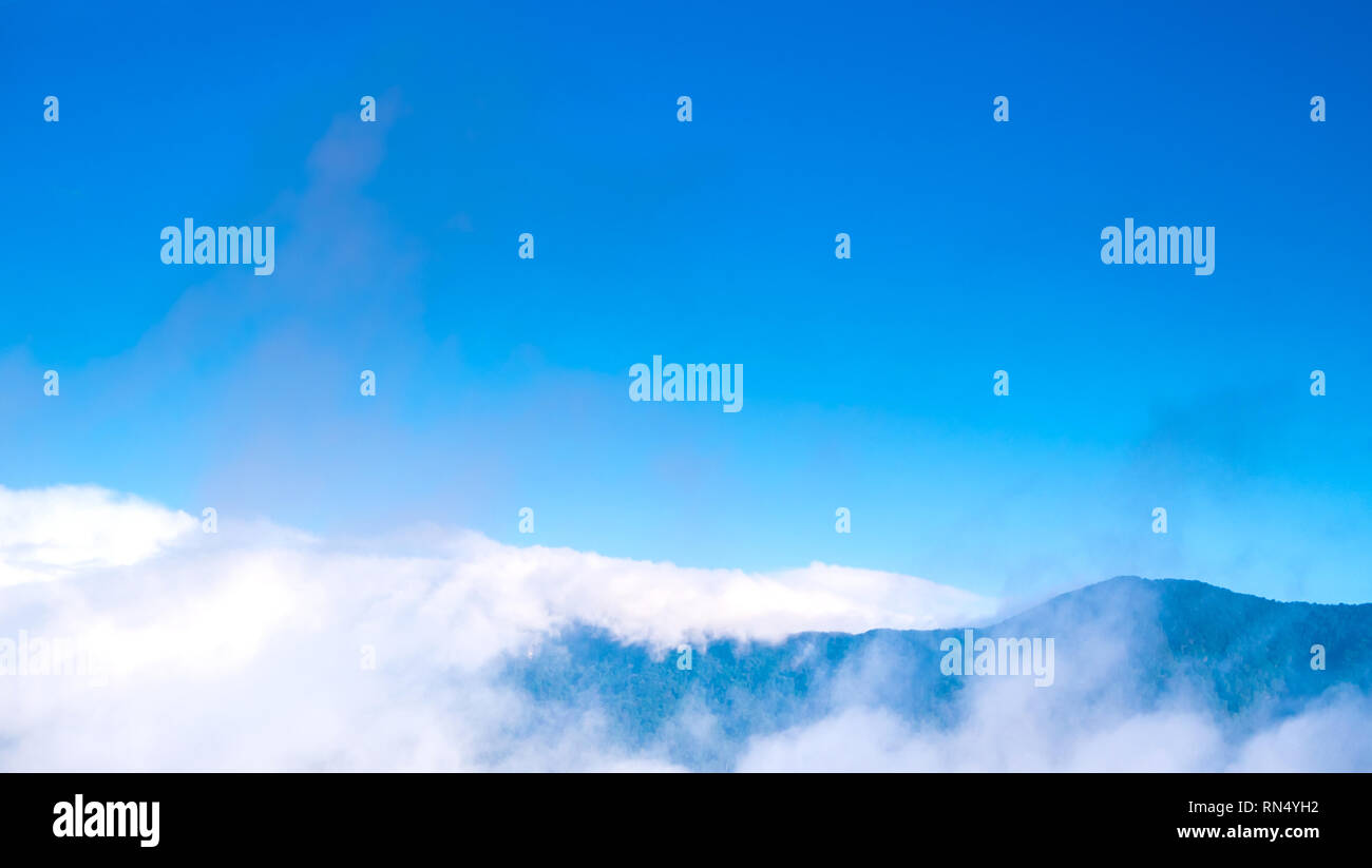 Cloudy floating above the big mountains - Stock Image