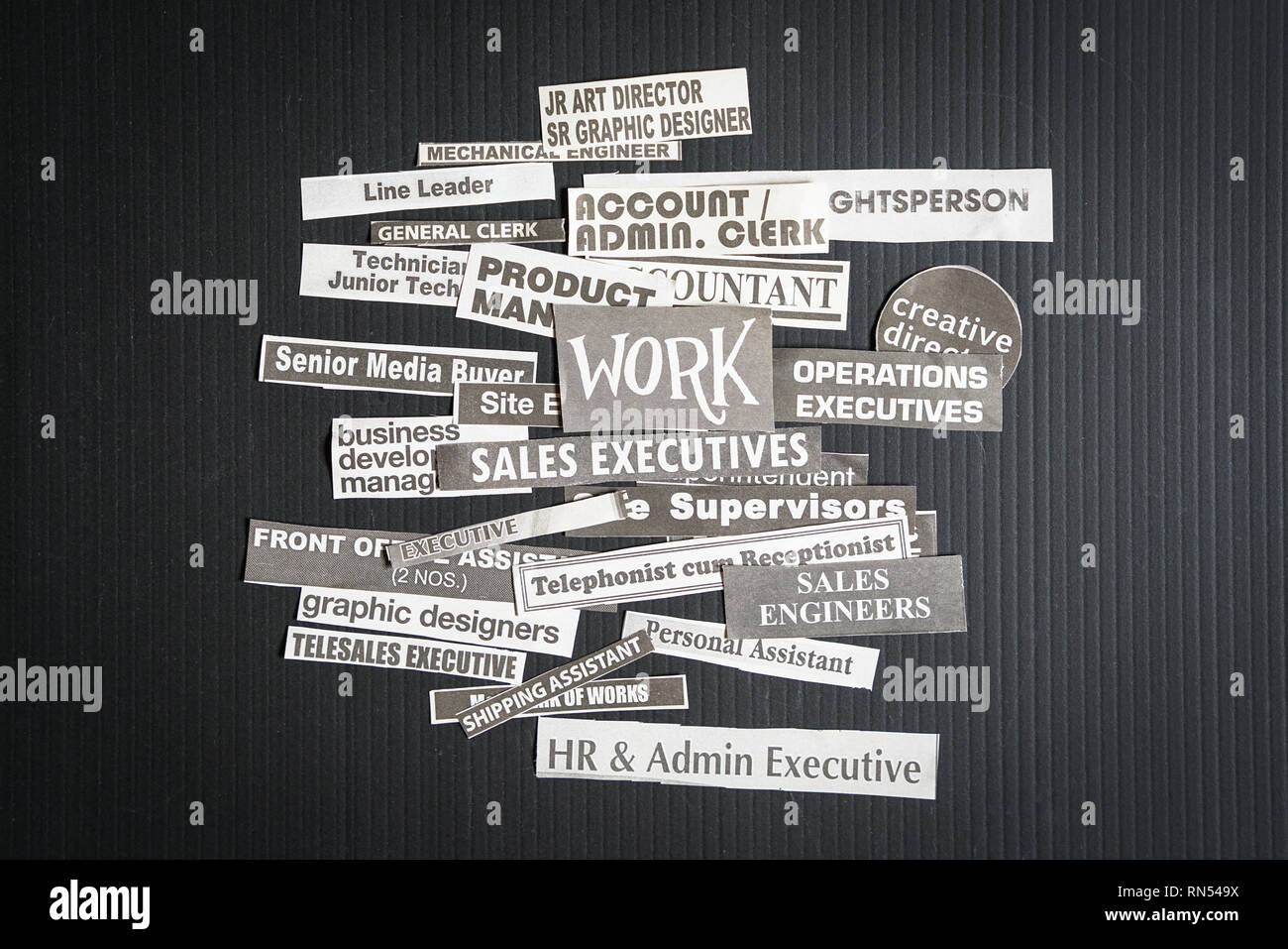 Jobs or careers concept: multiple job titles or occupations cut off from newspaper with Work on top of the pile and on black background - Stock Image