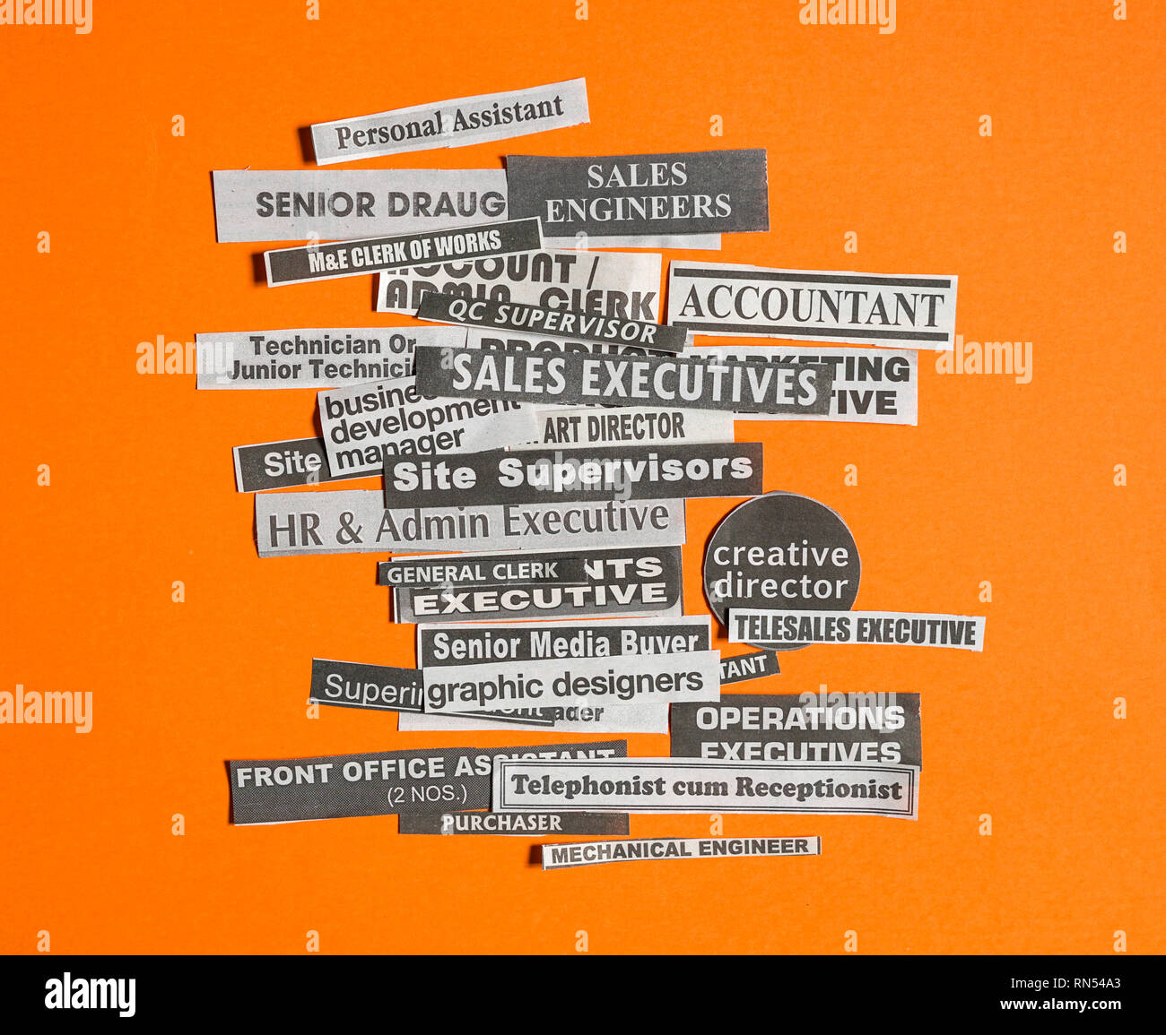 Jobs or careers concept: multiple job titles or occupations cut off from newspaper on orange background - Stock Image