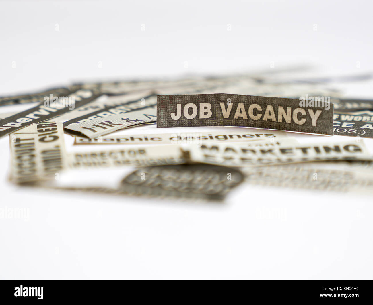 Jobs or careers concept: job titles or occupations cut off from newspaper and focus on Job Vacancy - Stock Image