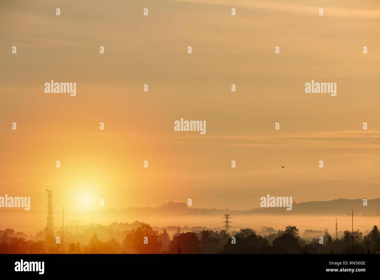 Orange sunrise over hills with mysty fog - Stock Image