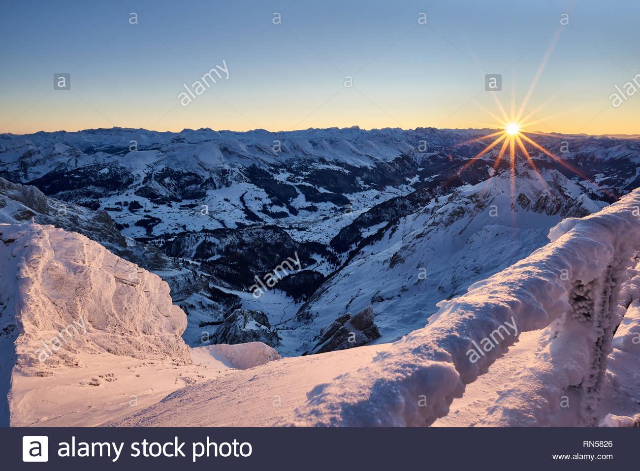 Blick vom Säntis bei Sonnenuntergang Richtung Toggenburg, Sonnenstrahlen, schneebedeckte Berge, Licht und Schatten, Panorama, Himmel - Stock Image
