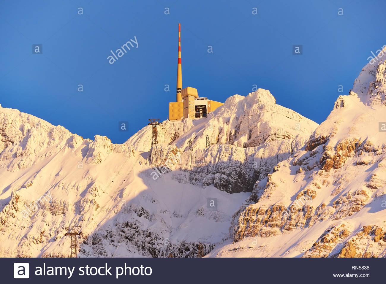 Säntis im Winter, Bergstation mit Sendemast, Nahaufnahme, schneebedecktes Felsmassiv im gelben Abendlicht, blauer Himmel, Seilbahnmasten - Stock Image